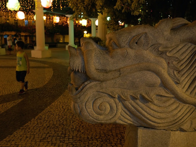 boy walking near a stone dragon in Taipa Village, Macau