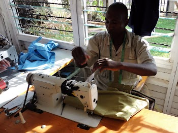 Boniface carefully sewing some trousers