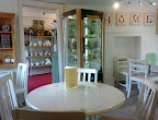 Clean brightly painted tearoom with marbled tables and curios