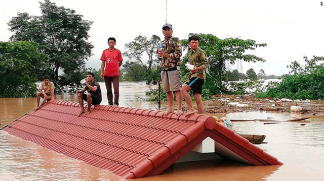Sanamxay villagers sought safety on the roofs of their houses to escape the flooding following the dam collapse on 23 July 2018. Photo: CNN