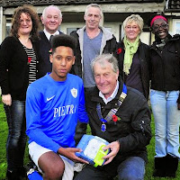 2nd November 2014 Holt FC player Quinton Barham receives the equipment from Lions president Brian Hersee watched by Holt Parish Council chairman Becky Stevens, Lions member Chris Penny, Holt Parish clerk Jenny Beale and Quinton's parents, Paul and Debra Barham