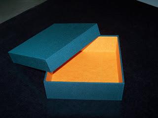 Gefügte Schachtel mit grünem Mattgewebe überzogen und mit Elefantenhautpapier in orange ausgefüttert