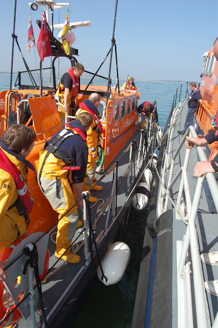 Crew members placing fenders during an alongside-tow exercise