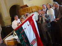 29 A zászlóanya, Gál Mária emlékszalagot köt a zászlóra, s újabb 3 szöget üt a rúdba.JPG