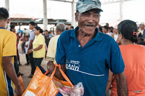 A man smiles joyfully  - he holds a bulging organge sack in his arm (which has been amputated below the elbow)