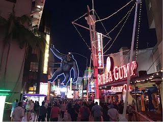 En gågate om kvelden med mye noenlys. En stor figur av King Kong henger over gaten.
