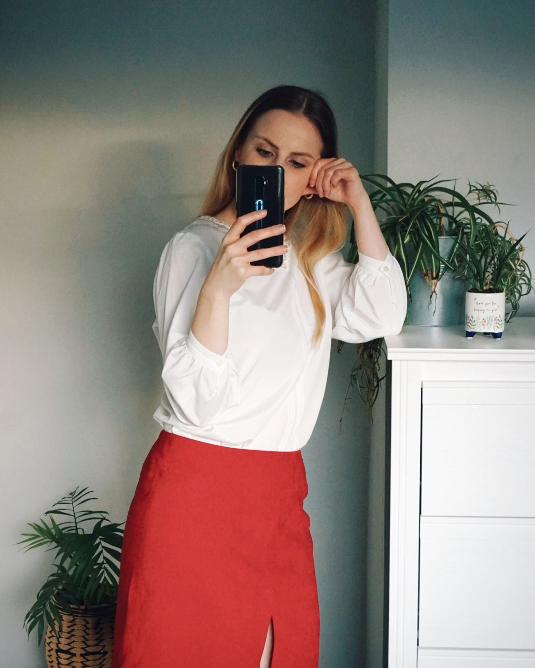 Amy is wearing a white blouse tucked into a red suede skirt