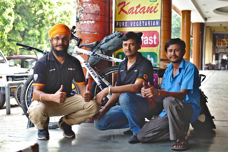 Cei 3 indieni mecanici si cele doua biciclete gata drum in spate.