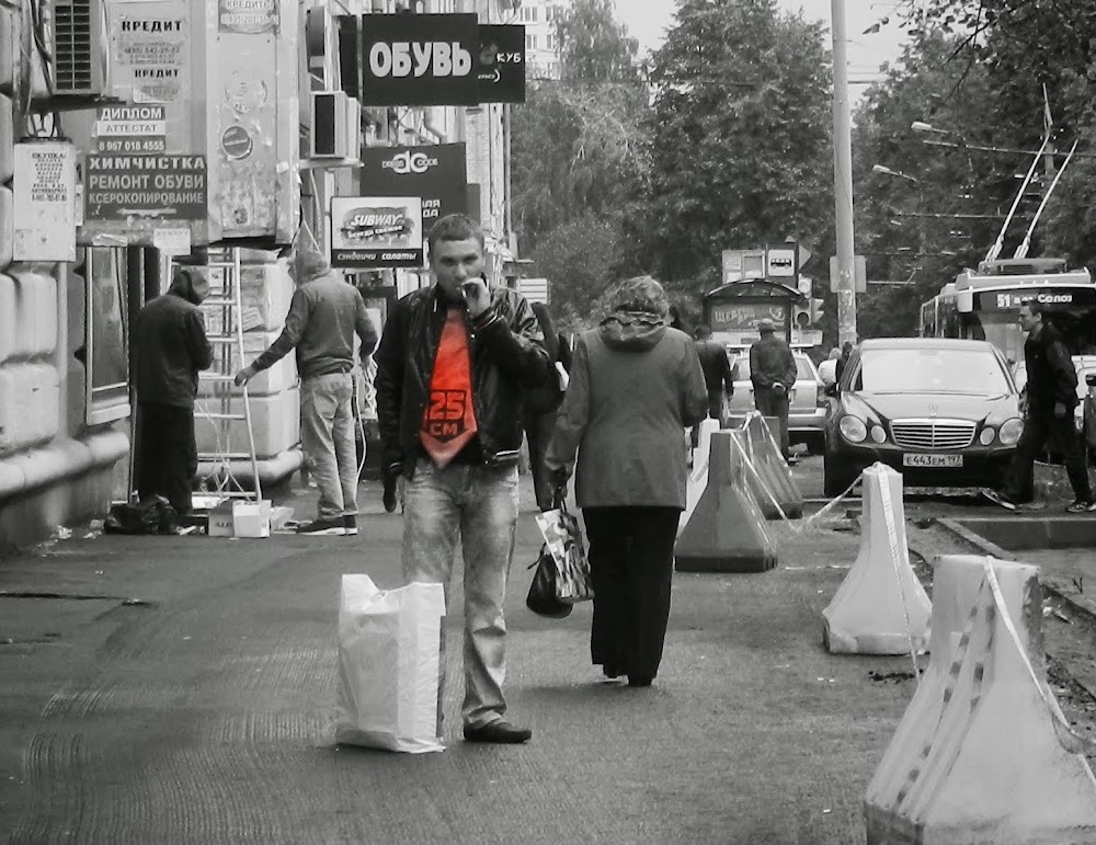 this guy was trying to sell something in his bag... the woman walking away declined the sale, and he promptly lit a cigarette