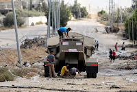 Palestinian men climb on Israel's military vehicle that was left behind by the forces in Gaza City's Shijaiyah neighborhood, Saturday, July 26, 2014. Thousands of Gaza residents who had fled Israel-Hamas fighting streamed back to devastated border areas during a lull Saturday to find large-scale destruction: scores of homes were pulverized, wreckage blocked roads and power cables dangled in the streets. (AP Photo/Hatem Moussa)