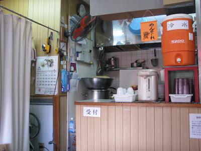 厨房の前に置かれたセルフサービスの冷水、左下には製麺機