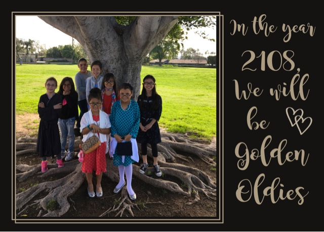 A group of third grade students gathered under a tree.
