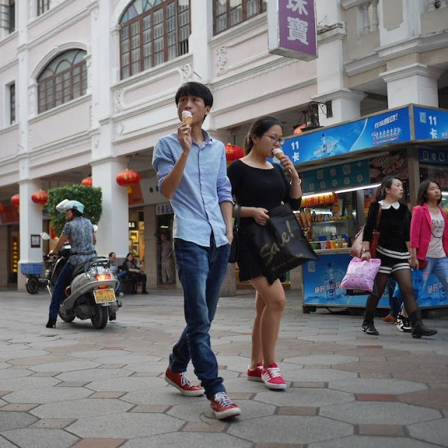 young man and young woman walking on a Sunwen West Road Pedestrian Street while eating ice cream