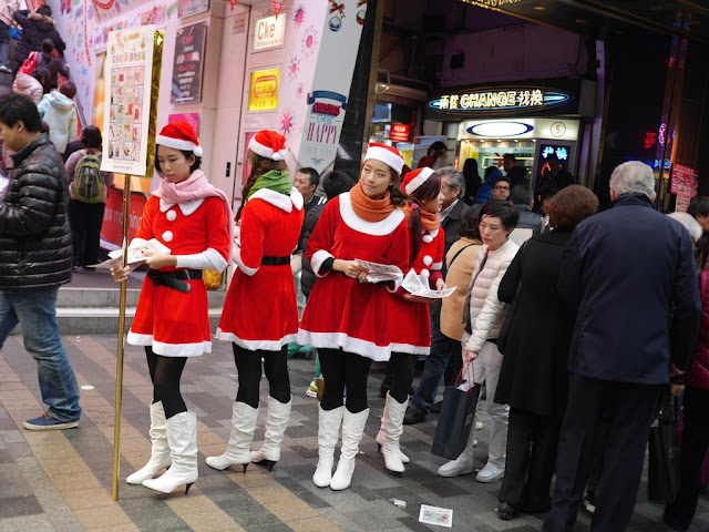 young women wearing Santa outfits handing out promotional material