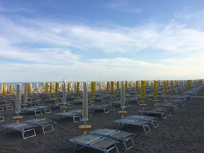 Sammenpakkede solsenger på stranda om kvelden.