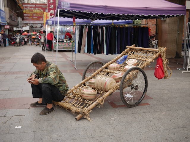"Man uses a mobile phone while sitting next to ""mobile"" pots in Nanxiong, Guangdong."