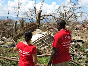 A man and woman (wearing shirts with 'CBM Emergency Response Team' looking at broken houses and fallen trees