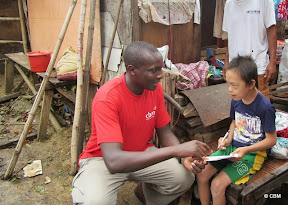 A man (wearing red CBM t-shirt) and a young boy sitting talking, surrounded by boxes, clothes, wood
