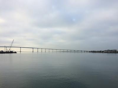 Stille vann med en bro i bakgrunnen.