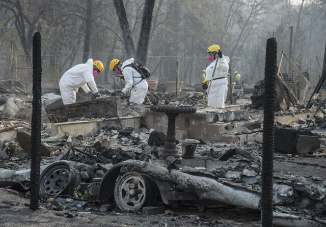 Members of the Mendocino County Sheriff's Department Search and Rescue, rake through ruins in Paradise, California, on Saturday, 17 November 2018. Photo: Terry Schmitt / UPI