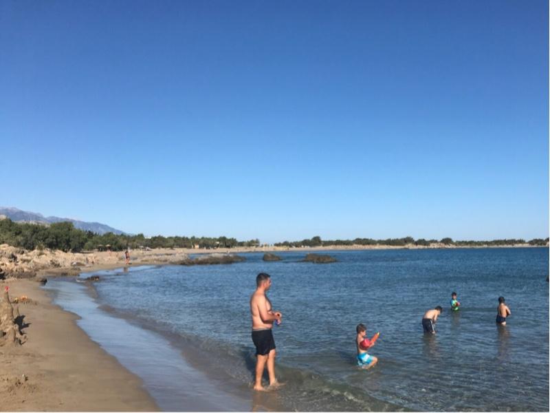 Lang sandstrand som også kurver seg rundt en bukt. Lavere vegetasjon bak stranden. Mennesker som bader.
