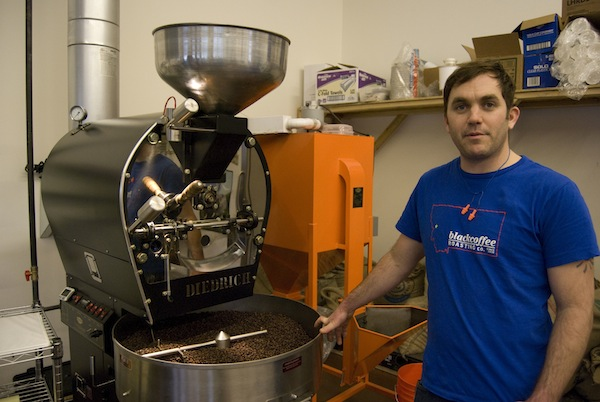 Matt McQuilkin stands next to BCRC's roaster. Behind him is a destoner, which removes debris from coffee after it has been roasting and before it is bagged.