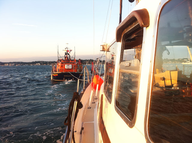 Poole all-weather Tyne class lifeboat towing a 9.5m motor sailing vessel that had overheated, with the owners fearing that it had caught fire. 19 August 2013 Photo: RNLI/Dave Riley
