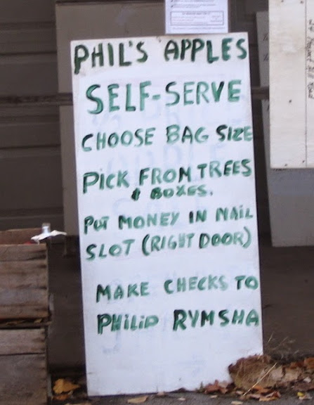 Hand-lettered sign that reads: Phil's Apples, Self Serve, Chosee Bag Size, Pick from Trees & Boxes, Put Money in Mail Slot (Right Door), Make Checks to Phil Rumsha