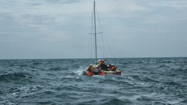 Two Poole crew members board the yacht from the Swanage D-class lifeboat - 28 September 2013. Photo credit: RNLI / Rob Inett