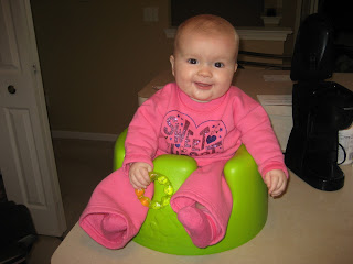 Cute child in a bumbo chair on a counter.