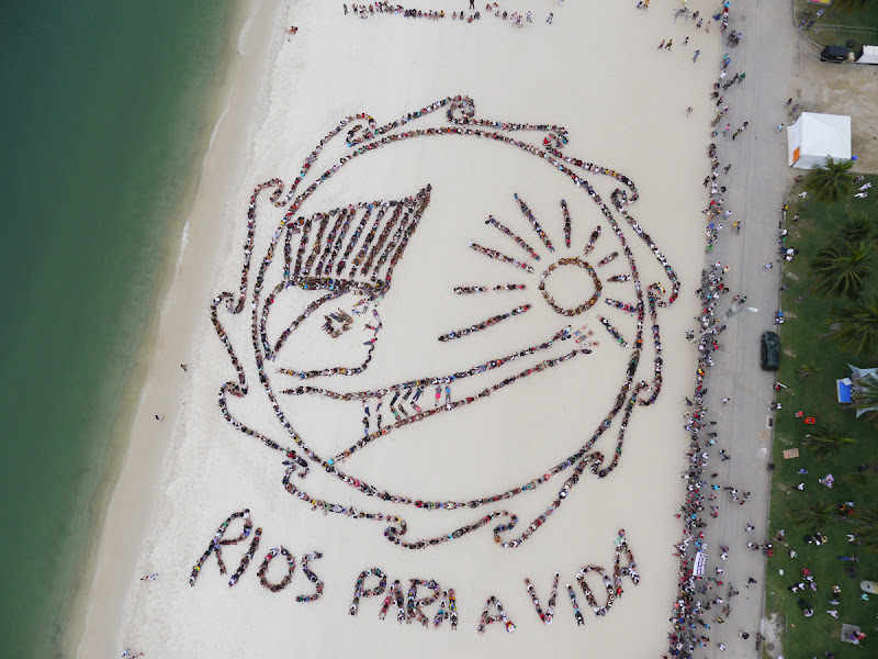 Nearly 1500 people used Rio's Flamengo Beach as a canvas on June 19, 2012. Their bodies formed the lines of an enormous image promoting the importance of free-running rivers, truly clean energy sources like solar power and including indigenous knowledge as part of the solution to climate issues. The activity was led by Brazil's many indigenous peoples organized under the umbrella of the Articulation of Brazilian Indigenous Peoples. ©Spectral Q/Chico/Paulo