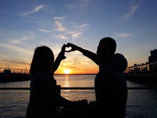 夕日に向かってハートを作る幸せなカップル