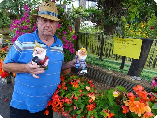Laurence Perry with two gnomes ripped from their base and the now empty wooden shelf at the front of his garden