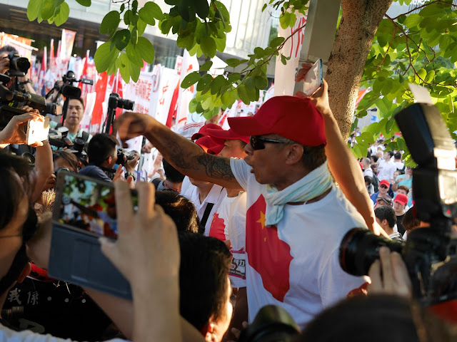 man wearing shirt with a Chinese flag yelling at people