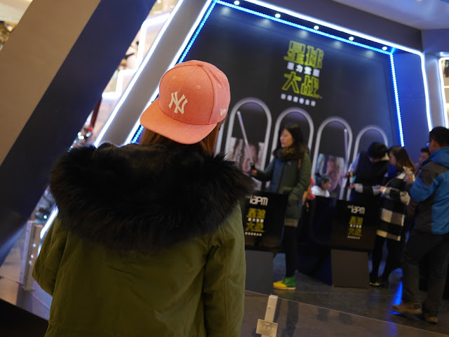 young woman wearing a ping New York Yankees hat looking at a Star Wars light saber display at the IAPM shopping center in Shanghai