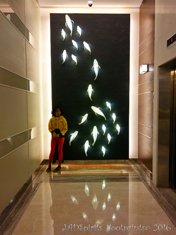 A welcoming sight of glowing koi on the wall by the elevators