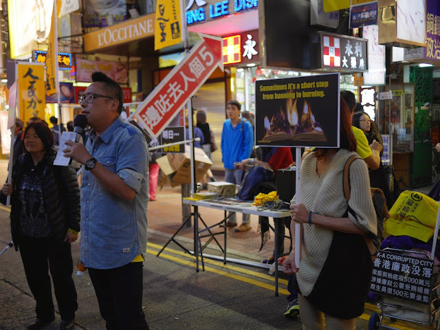 "Speaker next to a woman holding a sign reading ""Sometimes it's a short step from banning to burning"" at the People Power demonstration in front of Causeway Bay Books in Hong Kong"