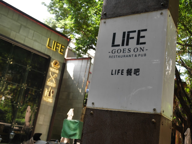 "sign for the ""Life Goes On Restaurant & Pub"" in Zhuhai"