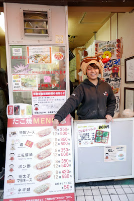 I went for the takoyaki stand Ganso Donaiya with the famous rotating takoyaki sign. And the lady taking orders is wearing a hat. And there are photos from articles and a Tripadvisor sticker on it. Must be good!