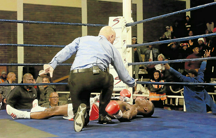 Lusanda Komanisi is counted out by referee Deon Dwarte after being dropped hard by Filipino Jhack Tepora in their bout at the Orient Theatre.