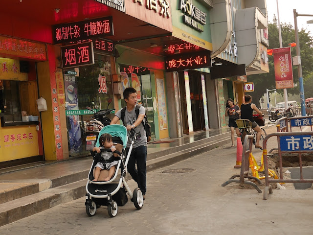 man pushing a girl in a stroller in Zhongshan, Guangdong