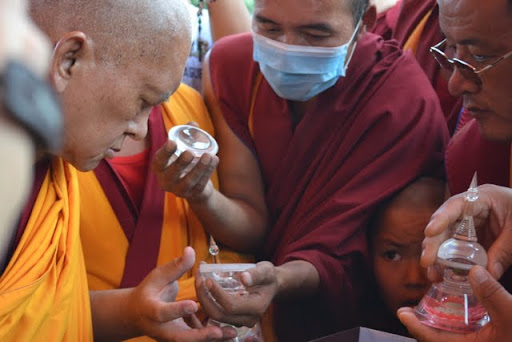 Lama Zopa Rinpoche examines Lama Lhundrup's relics. Photo by Ven. Thubten Sangmo.