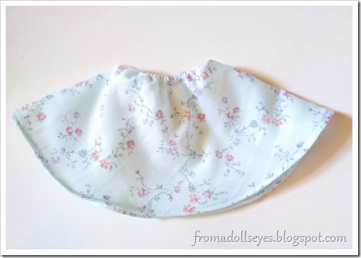 A half circle skirt made for a ball jointed doll.  It is made with a pale blue floral print fabric and has an a-line shape to it.
