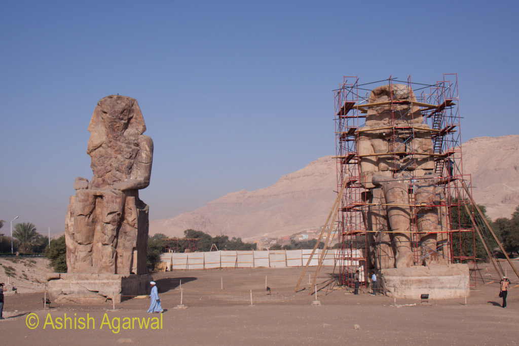 View of both statues of the Colossi of Memnon, with one of them being completely covered in scaffolding