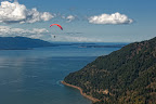 Please credit Paul K. Anderson A paraglider sails over the Chuckanut Range and the commercial oyster beds of Samish Bay as a coal train from the Powder River Basin in Wyoming rounds Pidgeon Point.