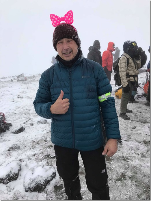 Roy Price at the top of Mount Kilimanjaro wearing a bow in memory of his wife Ruth