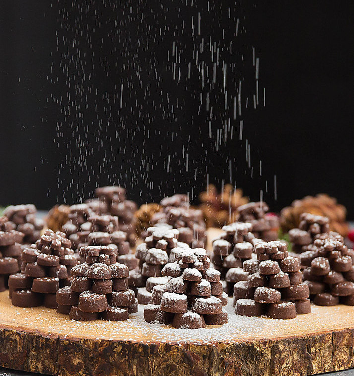 photo of powdered sugar falling on Chocolate Pinecone Shortbread Cookies