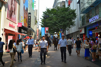 Photo: Police parade in the shopping street Myeong Dong and encourage tourists to take pictures of them