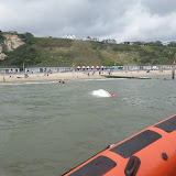 1 September 2012 - 2 ILB crew members hold a line to an upturned motorboat.  Photo credit: Poole RNLI/Dave Riley