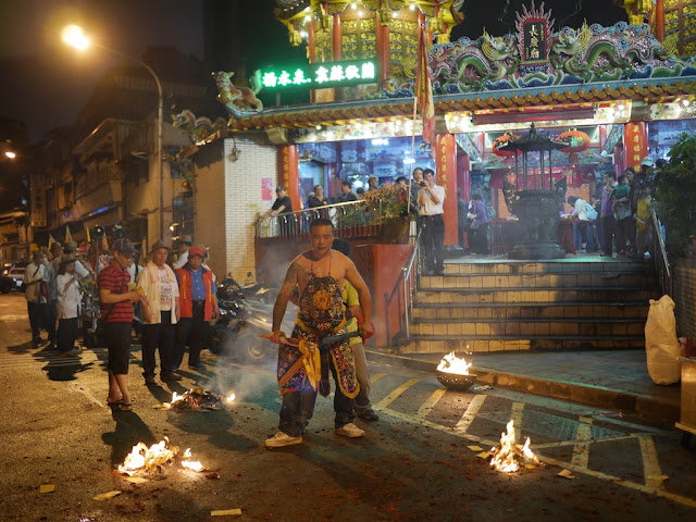 man holding swords and standing between several fires for a ceremony at the Chang Qing Temple (長慶廟) in Taipei